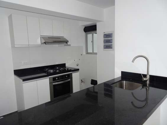 Cocina con muebles altos y bajos , tableros de granitos . equipado con cocina a gas . horno y campana extractora nuevos
